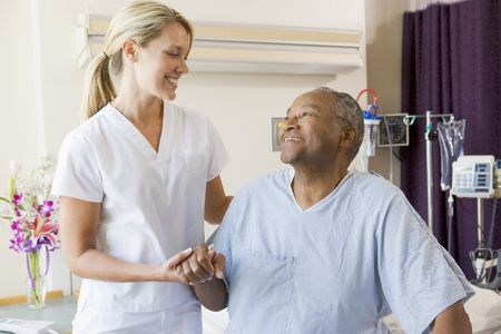 Nurse Helping Patient Sit Up In Bed Stock Photo - 3724727