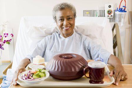 bandejas: Superior mujer sentada en la cama de hospital con una bandeja de comida
