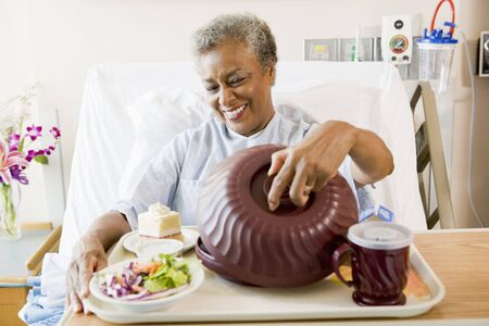 Senior Woman Sitting In Hospital Bed With A Tray Of Food photo