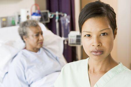 Nurse Standing In Patients Room Looking Serious Stock Photo - 3724046