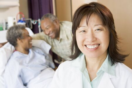 patient on bed: Nurse Smiling In Hospital Room Stock Photo