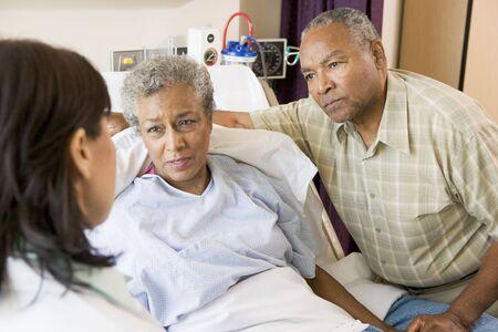 hombre preocupado: Doctor hablando con dos altos