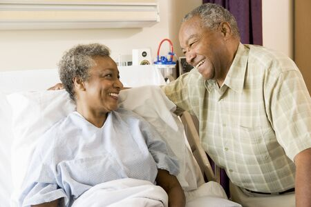 healthcare visitor: Senior Couple Smiling At Each Other In Hospital Stock Photo