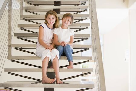 7 year old girl: Two Young Girls Sitting On A Staircase At Home