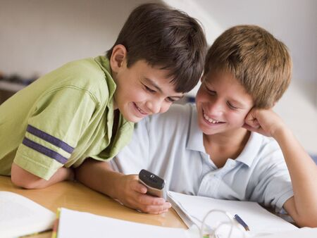 Two Young Boys Distracted From Their Homework, Playing With A Cellphone photo