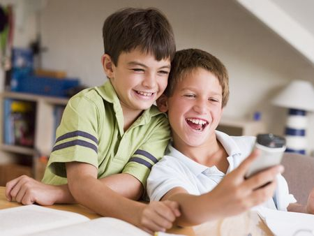 hp: Two Young Boys Distracted From Their Homework, Playing With A Cellphone