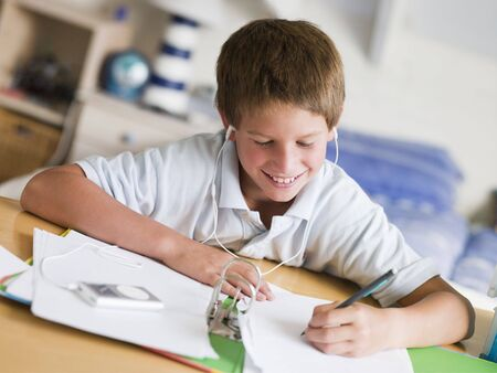 preadolescent: Young Boy Doing His Homework While Listening To Music On His MP3 Player Stock Photo