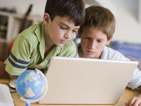 learning computer: Due Young Boys Utilizzando un computer portatile a casa