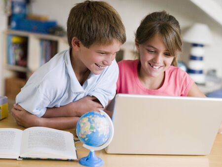 Boy And Girl Doing Their Homework On A Laptop photo
