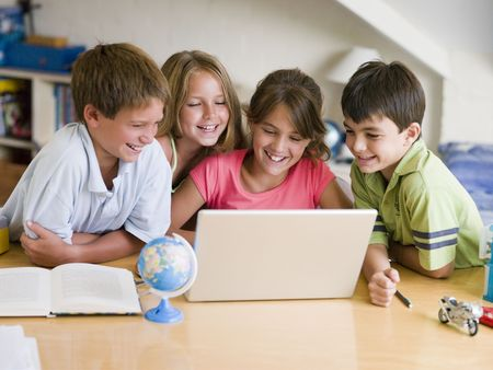 Group Of Young Children Doing Their Homework On A Laptop photo