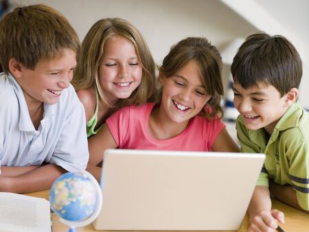 preadolescent: Group Of Young Children Doing Their Homework On A Laptop
