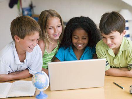 Grupo de niños haciendo sus tareas en un ordenador portátil Foto de archivo - 3728304