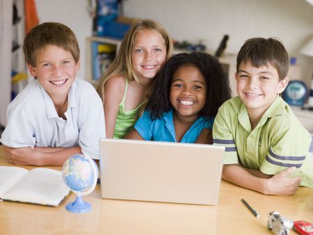 ni�os sentados: Grupo de ni�os haciendo sus tareas en un ordenador port�til