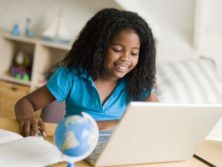 9 year old: Young Girl Doing Her Homework On A Laptop Stock Photo