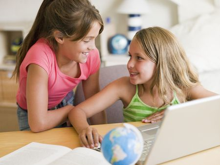 Two Young Girls Doing Homework On A Laptop photo