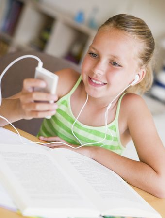 Young Girl Distracted From Her Homework, Playing With An MP3 Player photo