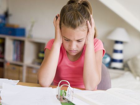 preadolescent: Young Girl Doing Her Homework With Her Head In Her Hands
