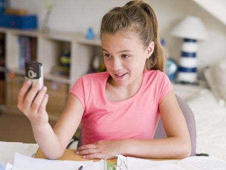 mobilephones: Young Girl Distracted From Her Homework, Playing With A Cellphone Stock Photo