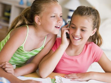 Young Girls Distracted From Their Homework, Talking On A Cellphone Stock Photo - 3728339