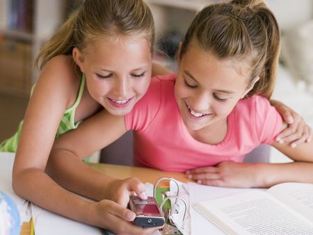 sms text: Young Girls Distracted From Their Homework, Playing With A Cellphone