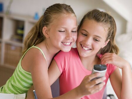 send sms: Young Girls Playing With A Cellphone Stock Photo