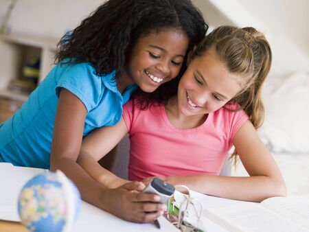 caucasian race: Young Girls Distracted From Their Homework, Playing With A Cellphone