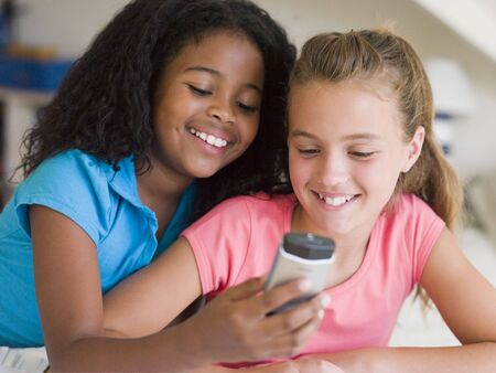 9 year old girl: Young Girls Playing With A Cellphone Stock Photo