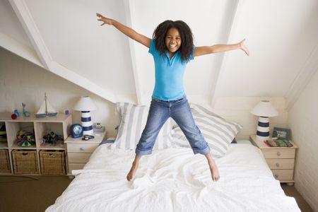 persona saltando: Joven muchacha saltando en la cama