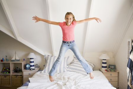 preteen girl: Young Girl Jumping On Her Bed