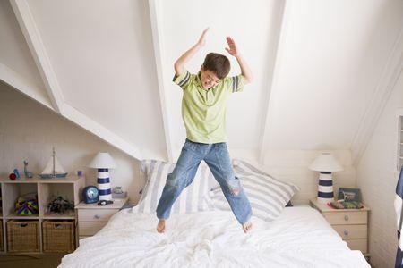 ni�o saltando: Joven muchacho saltar sobre su cama