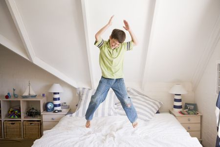 elementary age boy: Young Boy Jumping On His Bed