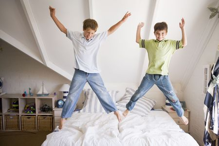 boy jumping: Joven muchacha saltando en la cama