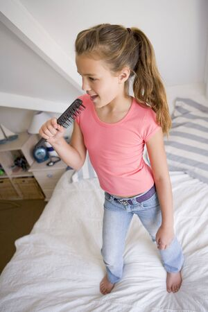 Young Girl Standing On Her Bed, Singing Into Her Hairbrush photo