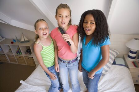 preteen girl: Three Young Girls Standing On A Bed, Singing Into A Hairbrush