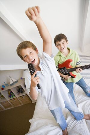 elementary age boy: Two Boys Standing On A Bed, Playing Guitar And Singing Into A Hairbrush Stock Photo