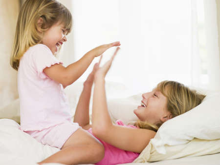 Young Girl Being Woken Up By Her Little Sister photo