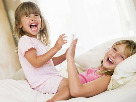 woken: Young Girl Being Woken Up By Her Little Sister Stock Photo