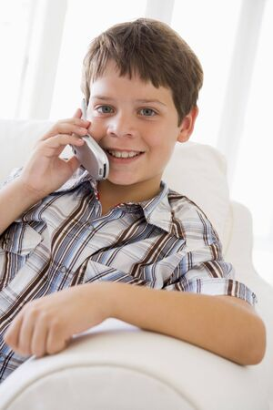 Young Boy Sitting On A Sofa Talking On A Mobile Phone photo