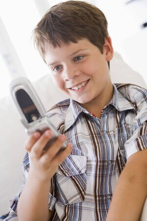 Young Boy Sitting On A Sofa Texting On A Mobile Phone photo
