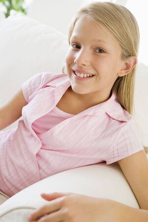preteen girl: Young Girl Sitting On A Sofa Stock Photo