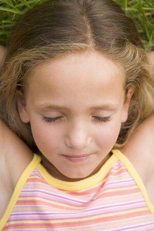 girl lying down: Ni�a acostada en la hierba