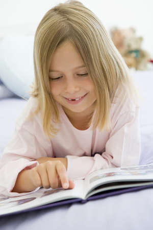 Young Girl Lying On Her Bed In Her Pajamas, Reading A Book photo