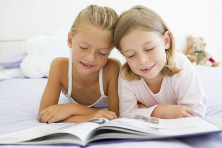 Two Young Girls In Their Pajamas, Reading A Book photo