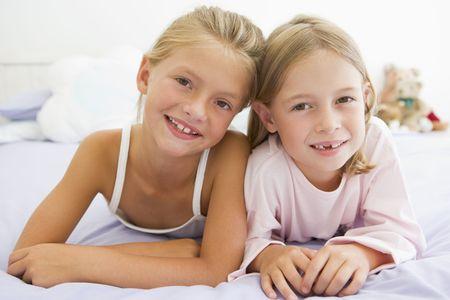 pajamas: Dos muchachas j�venes en sus pijamas acostado en una cama