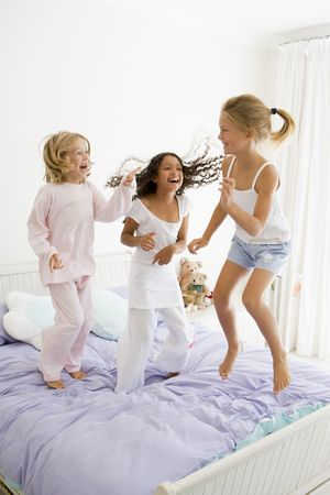 Three Young Girls Jumping On A Bed In Their Pajamas photo