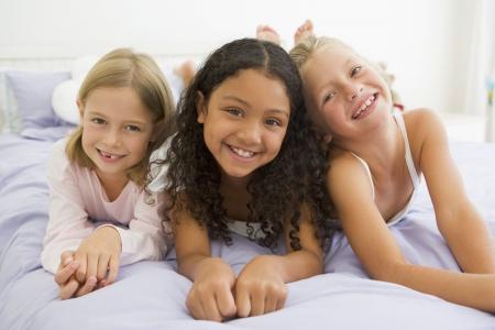 pijamada: Tres niñas acostado en una cama en su pijama Foto de archivo
