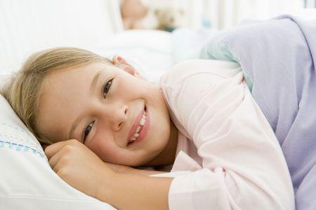 girl lying down: Ni�a acostada en su cama Foto de archivo