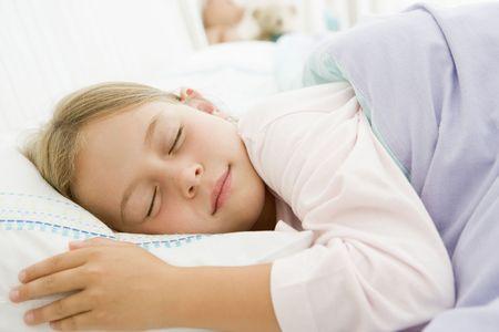 pijama: Ni�a dormida en su cama Foto de archivo