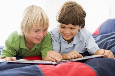 Two Young Boys Lying Down On A Bed Reading A Book photo