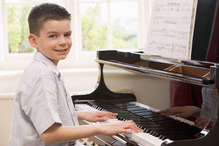 tocando el piano: Chico tocando el piano Foto de archivo